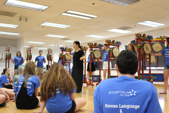Students seated on the floor of a dance studio learning Korean drumming from a Korean instructor.